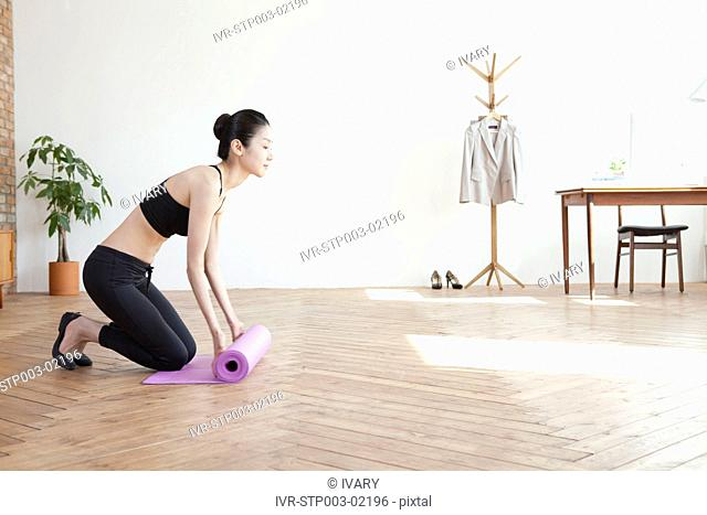 Asian Woman Arranging The Exercise Mat On Harwood Floor