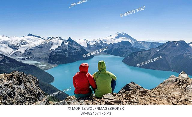 View from Panorama Ridge trail, Two hikers sitting on a rock with Garibaldi Lake, turquoise glacial lake, Guard Mountain and Deception Peak, back glacier