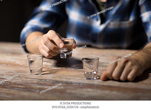 hands of alcoholic drinking vodka shots at night