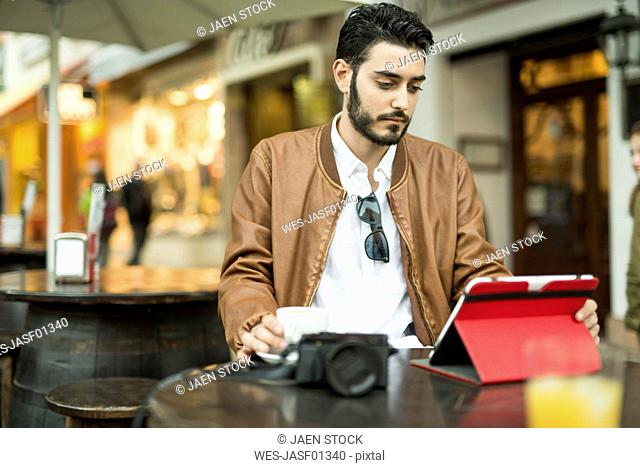 Young man using tablet at outdoor cafe