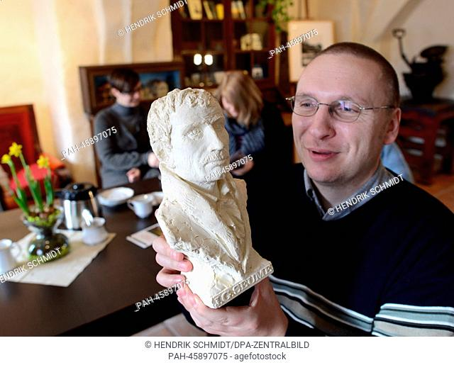 A portrait bust of Johann Gottfried Seume is held by Thorsten Bolte in the reopened Seume house in Grimma, Germany, 29 January 2014