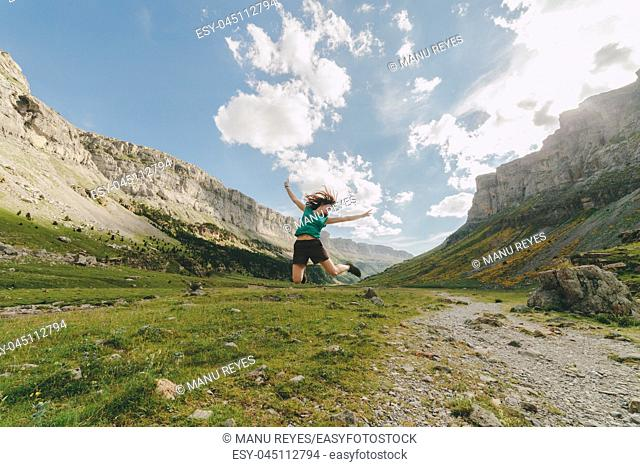 Young redhead woman jumping in a big valley, in Ordesa, Huesca, concept of freedom