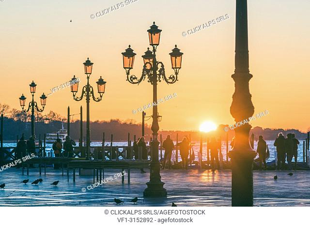St Mark's square, Venice, Veneto, Italy. Tourists admiring the sunrise over St. Mark's waterfront