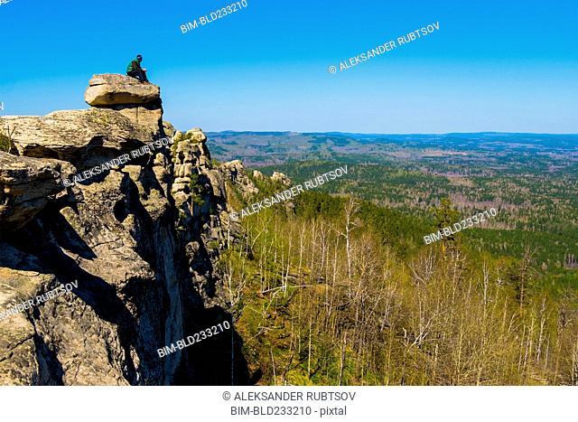 Caucasian man sitting on mountain rock admiring scenic view
