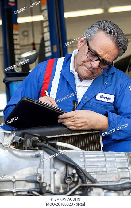 Mechanic writing down something on clipboard