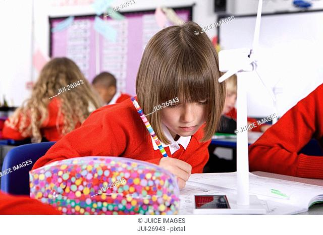 Serious school girl writing in notebook in classroom with wind turbine on desk