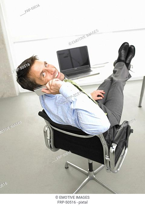 Telephoning business man having his legs on his desk