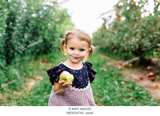 Young girl wearing dress standing in an orchard, holding apple, smiling at camera