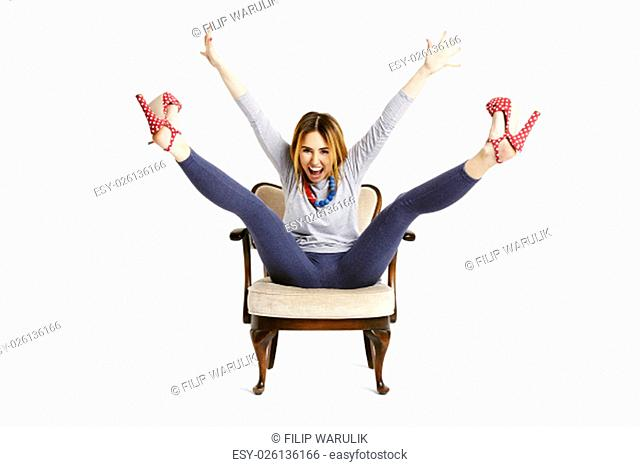 Enjoying a girl raises her arms and legs up. Isolated on white background