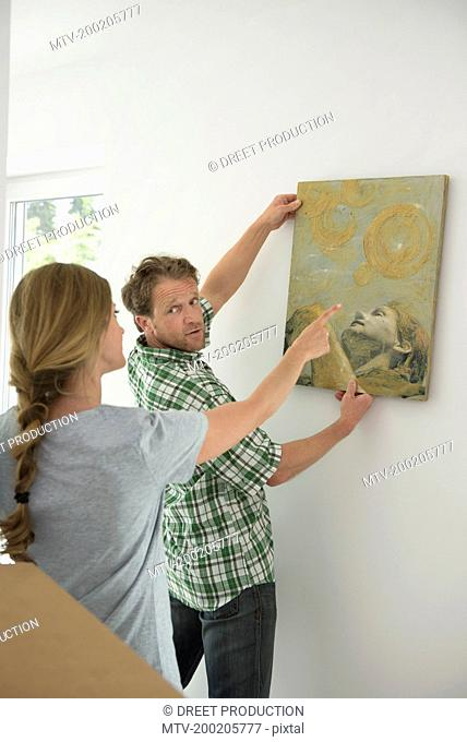 Man hanging painting woman helping explaining