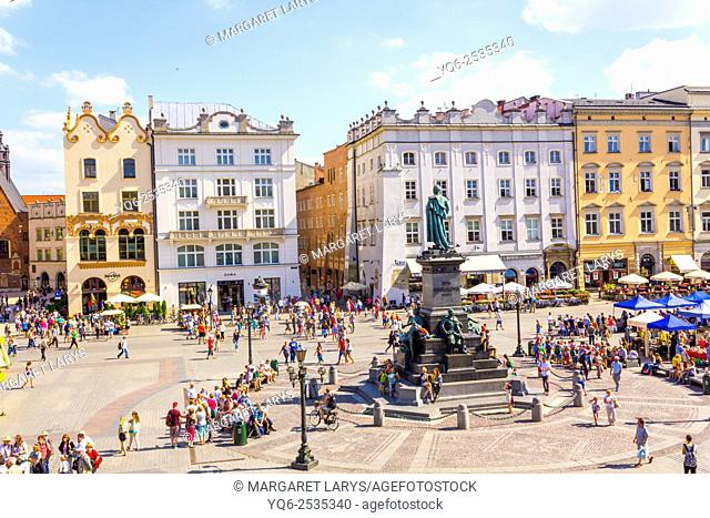 Adam Mickiewicz monument and tourists walking in the Old Market Square, and beautiful tenement houses, view from above, Krakow, Poland