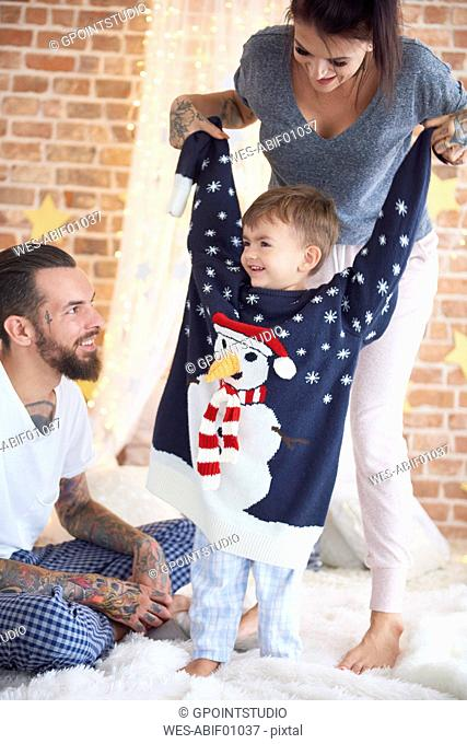 Boy trying on oversized Christmas Sweater with parents in bed