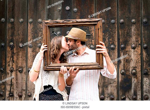 Portrait of couple, kissing, holding wooden frame in front of their faces, Mexico City, Mexico
