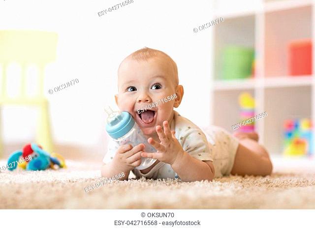 Cute baby boy drinking from bottle. Kid lying on carpet in nursery at home. Smiling child is 7 months old