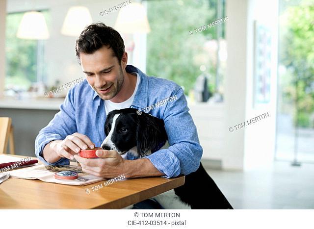 Man feeding dog at kitchen table