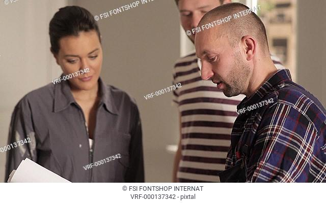 CU, R/F, Handheld of young couple and a contractor reviewing blueprints