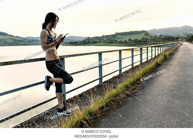 Female athlete checking smart phone leaning on railing