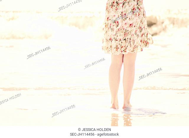 Low-section of girl (10-12) standing on beach