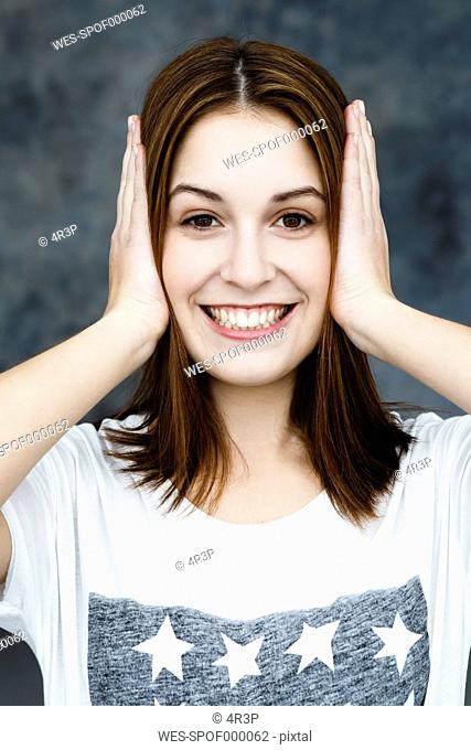Portrait of young woman covering ears, smiling
