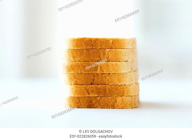 food, junk-food and unhealthy eating concept - close up of white sliced toast bread pile on table