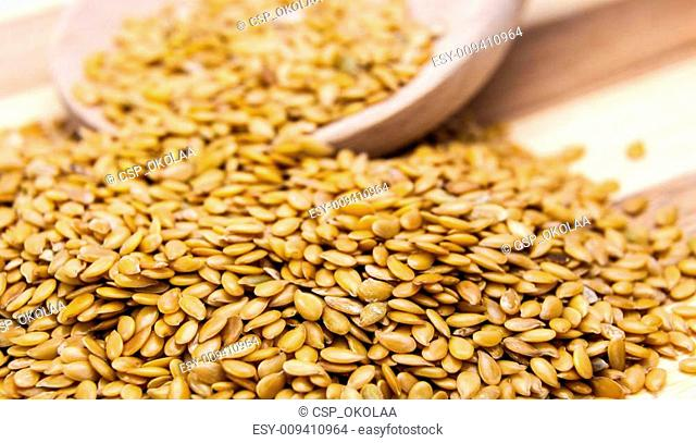 Golden flax seed spilled on table