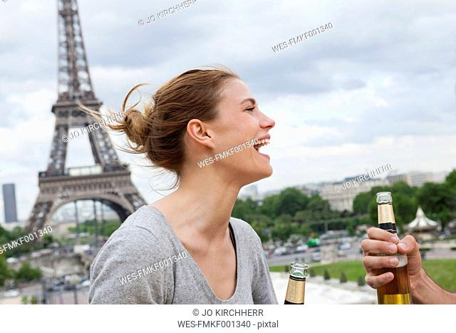 France, Paris, portrait of laughing woman in front of Eiffel Tower