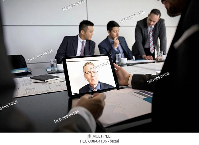 Male architect video conferencing on laptop in conference room