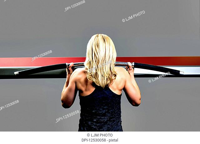 A middle-aged woman working out at a fitness facility doing chin-ups; Spruce Grove, Alberta, Canada