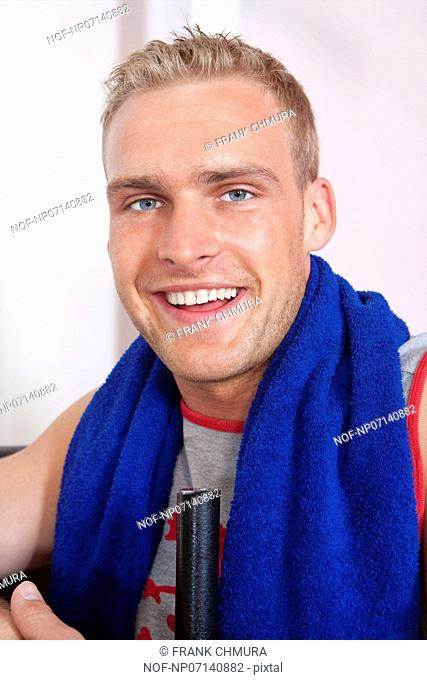 portrait of a young man with towel in modern gym