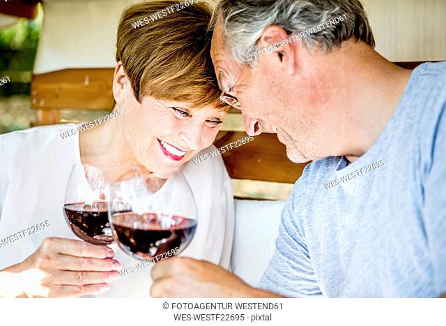 Happy senior couple having glass of red wine