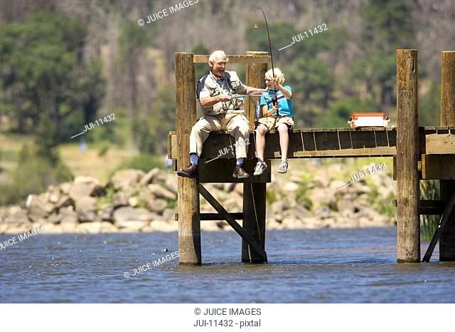 Boy 10-12 fishing with grandfather on jetty