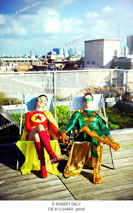 Superhero couple sitting on city rooftop