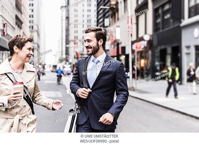 USA, New York City, businessman and woman walking in Manhattan