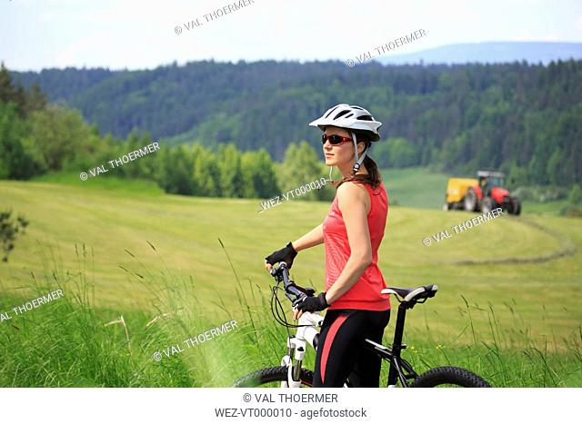 Germany, Mid adult woman standing with bicycle in forest