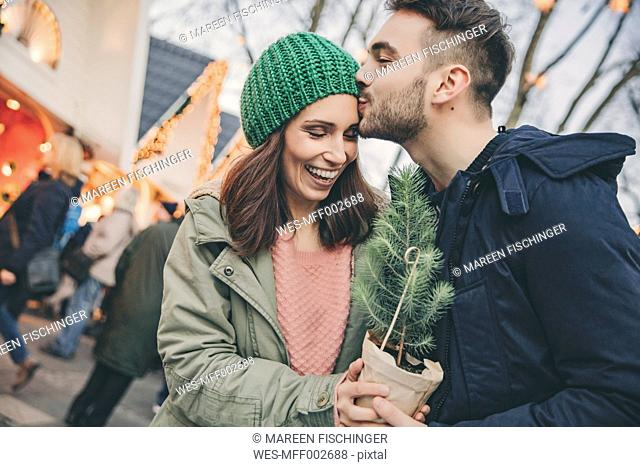 Man giving a small tree to a woman on the Christmas Market