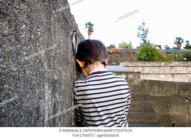 7 year old sad leaning against the wall