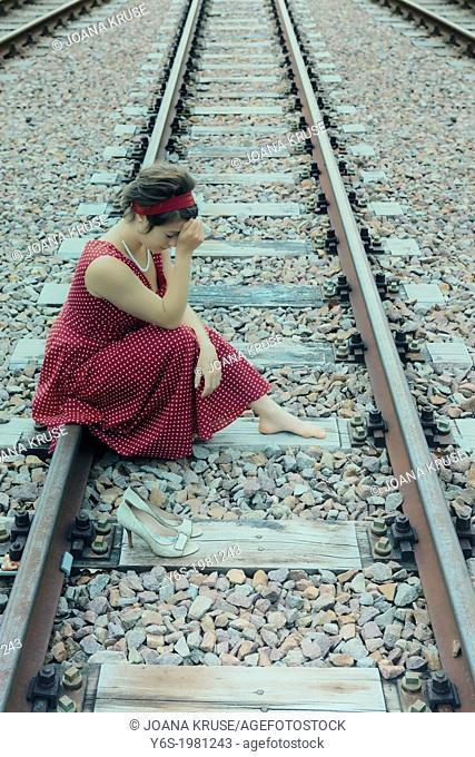 a sad girl on railway tracks