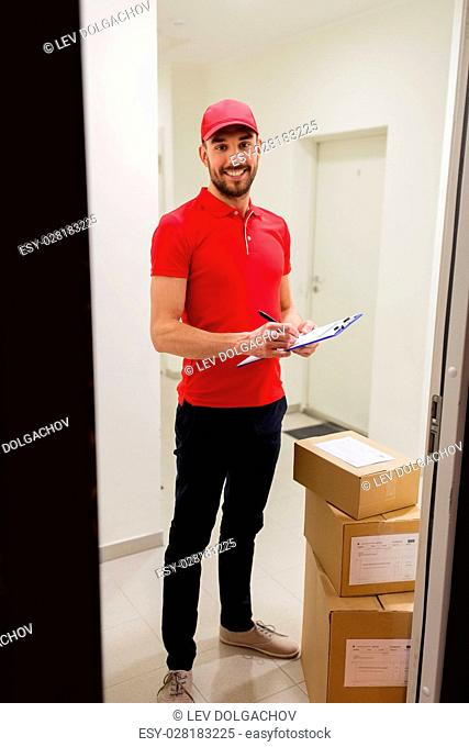 delivery, mail, people and shipment concept - happy man in red uniform with parcel boxes and clipboard in corridor at open customer door