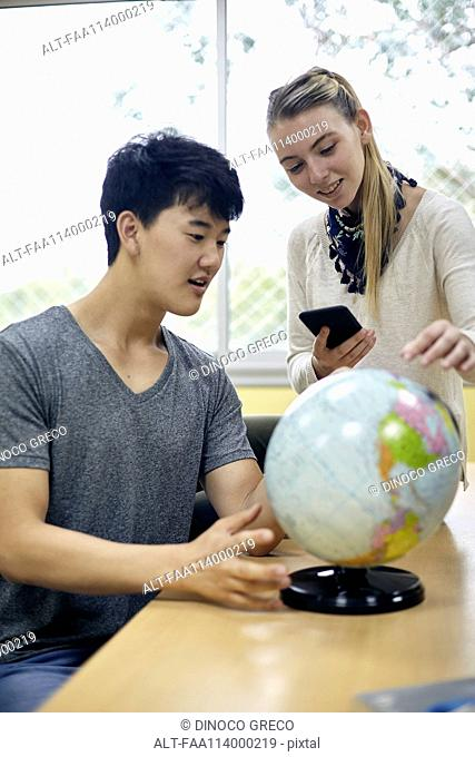 Students looking at globe in class