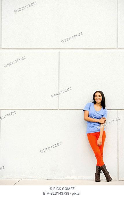 Black woman smiling near concrete wall