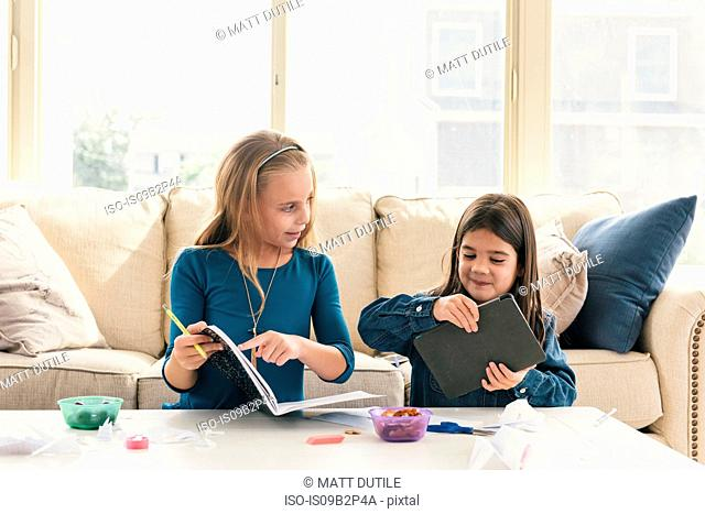 Girls at home using digital tablet, doing homework