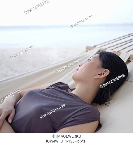 Side profile of a young woman relaxing in a hammock