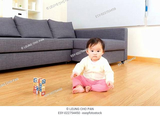 Asian baby girl play toy block at home