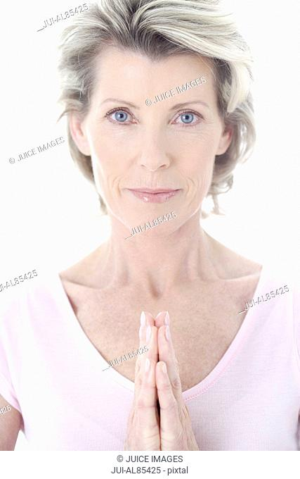 Close up of senior woman with hands pressed together