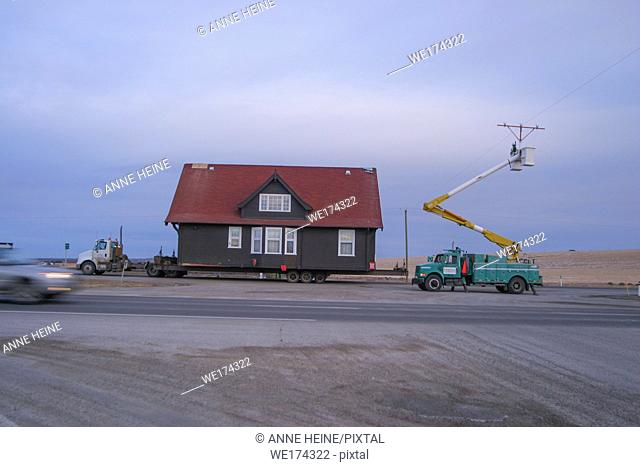 House moving along highway, crane in front pulls up powerline, Alberta, Canada