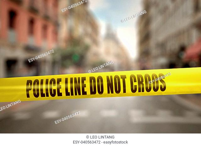 Yellow police line tape with text Police Line Do Not Cross against blurred city background