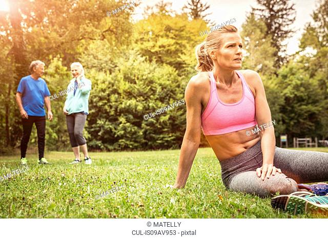 Mature women in park wearing sports clothing sitting on grass looking away