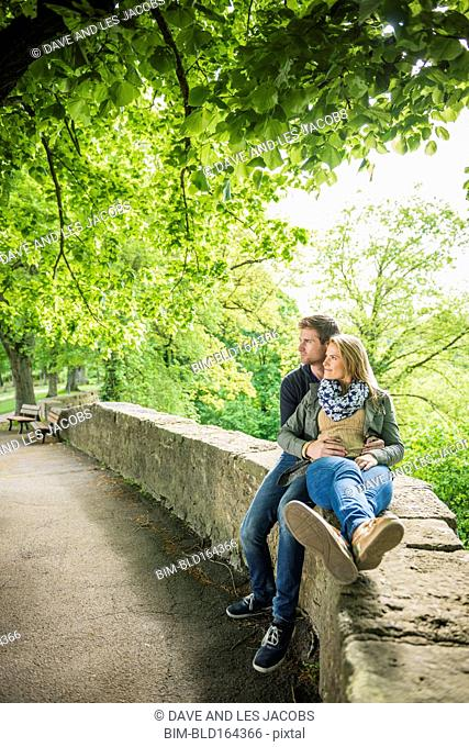 Caucasian couple relaxing on stone wall in park