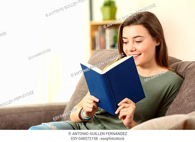 Portrait of a happy teenager reading a book on a sofa in the living room at home