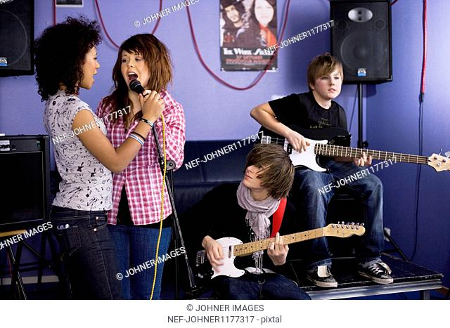 Teenagers playing guitars and singing